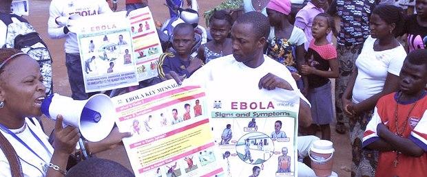 Personas de color mostrando carteles sobre el ébola. Foto: ONU